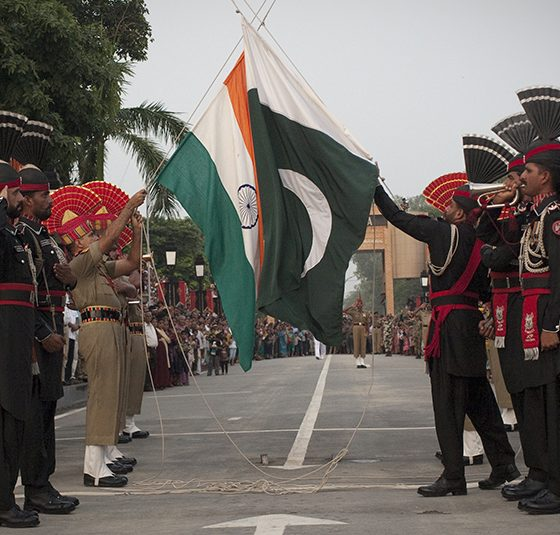 Pakistani and Indian soldiers lower the